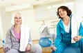 Sport break portrait of two mature women with bottles of water sitting in club Royalty Free Stock Image