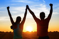 Sport couple of athletes success successful young raising arms to golden summer sunset sky after training fitness men and women Stock Photography
