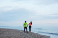 Sport couple walking along the beach resting after workout sexy fit women and men dressed in fluorescent shirt taking break Stock Images