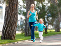 Sport family. Mother and baby daughter jogging run on nature
