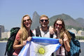 Sport fans friends in rio de janeiro holding argentinian flag group of backpackers traveling at with christ redeemer the Royalty Free Stock Photos