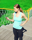 Sport and fitness concept - beautiful young woman listens to music and using smartphone in city Royalty Free Stock Photo