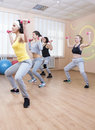 Sport and Fitness Concepts. Four Professional Sportswomen Having Trunk Bending Exercises with Barbells. Training In Sport Class. Royalty Free Stock Photo