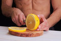 Sport, fitness, diet food, healthy lifestyle. Shirtless muscular man cutting grapefruit, fruits. Vitamin C products Royalty Free Stock Photo