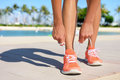 Sport fitness exercise lifestyle running concept and runner woman lacing shoes trainers tying laces before jogging on a Royalty Free Stock Photos