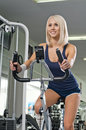 Sport fitness happy cutie athletic girl execute exercise on exercise bicycle and smile in hall Stock Photography