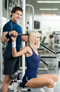 Sport fitness happy cutie athletic girl and guy execute exercise on apparatus in hall Stock Photography