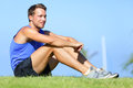 Sport fitness man relaxing after training outdoor young male athlete resting sitting in grass running and Stock Photos