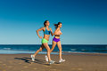 Sport and fitness people jogging on beach two women doing the in their vacation the sea Royalty Free Stock Photography