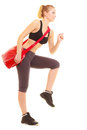 Sport fitness sporty girl with gym bag running to training and active lifestyle full length of red isolated on white Stock Photography