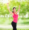 Sport fitness woman excited smile raised arm up happy hold hand young healthy girl perfect figure slim body over green tree Stock Photography
