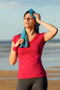 Sport fitness woman tired and sweating athlete wiping sweat from her forehead with a towel after running in summer on beach girl Royalty Free Stock Images