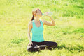 Sport, fitness, yoga concept - woman sitting on grass and drinking water from bottle in summer day Royalty Free Stock Photo