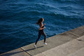 Sport girl in action running over ocean waves background Royalty Free Stock Photo