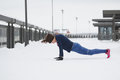 Sport girl model doing pushups during work out fitness at snow winter outdoor Royalty Free Stock Photo