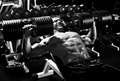 Sport guy very power athletic execute exercise press with dumbbells in hall black and white photo Stock Image