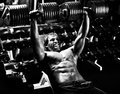 Sport guy very power athletic execute exercise press with dumbbells in hall black and white photo Stock Photo