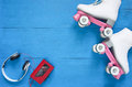 Sport, healthy lifestyle, roller skating background. White roller skates, headphones and vintage tape player. Flat lay, top view. Royalty Free Stock Photo