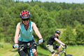 Sport mountain couple biking uphill sunny meadows Royalty Free Stock Image