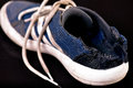 Sport shoe eaten by dog on black background white soled blue Stock Images