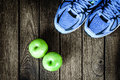 Sport shoes, Apples and bananas  on a  wooden background. Sport Royalty Free Stock Photo