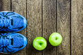 Sport shoes, Apples  on a  wooden background. Sport Royalty Free Stock Photo
