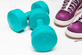 Sport shoes and  blue dumbbell on white background Royalty Free Stock Photo