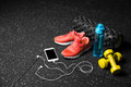 Sport shoes, dumb-bells, pilates mat, blue bottle, and phone with headphones on a black background. Training concept.