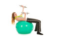 Sport woman with ball lifting dumbells for gymnastics heavy over white background Stock Photos