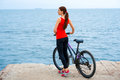 Sport woman with bicycles on the beach in red shirt standing concrete seacoast Royalty Free Stock Images