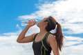 Sport woman holding a water bottle after exercise,back ground blue sky. Royalty Free Stock Photo