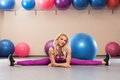 Sport woman sits on a twine. Athletic girl doing stretching exercise in the fitness room