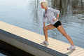Sport woman stretch body on water pier Royalty Free Stock Photo