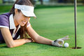 Sporting cheat female golfer pushing ball in hole Stock Photo