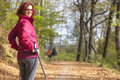 Sportive cute woman nordic walking autumn cross country mid aged female hiker resting whilst under the blue sky of the morning sun Stock Image