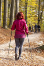 Sportive cute woman nordic walking autumn cross country mid aged female hiker under the blue sky of the morning sun in the forest Stock Photo