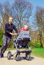 Sportive mother and baby jogging with her smiling toddler in a buggy Stock Photos