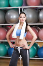 Sportive sexy woman in fitness gym with shelves of balls Royalty Free Stock Image