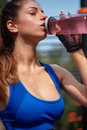 Sportive woman drinking vitamin water. Close up shot Royalty Free Stock Photo