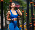 Sportive woman drinking vitamin water at the street gym