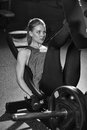 Sportive woman using weights press machine for legs gym at the pretty brunette exercising in a simulator working her quads at Stock Images