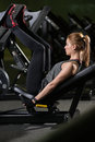 Sportive woman using weights press machine for legs gym at the pretty brunette exercising in a simulator working her quads at Royalty Free Stock Photo