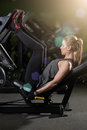 Sportive woman using weights press machine for legs. Gym. Royalty Free Stock Photo