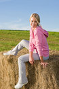 Sportive young woman relax on bales sunset Royalty Free Stock Image
