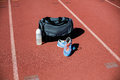 Sports bag, shoes and a water bottle kept on a running track Royalty Free Stock Photo