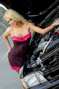 Sports car blonde fashion model in sexy dress checking out the engine in a black Stock Images