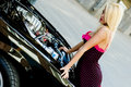 Sports car blonde fashion model in sexy dress checking out the engine in a black Royalty Free Stock Photos