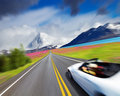 Sports car in motion blur mountain landscape with road and Royalty Free Stock Photo