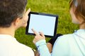Sports couple using digital tablet sitting on the grass a after training Royalty Free Stock Photography
