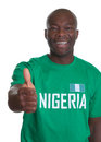 Sports fan from nigeria showing thumb up laughing soccer looking at camera and on an isolated white background Royalty Free Stock Images